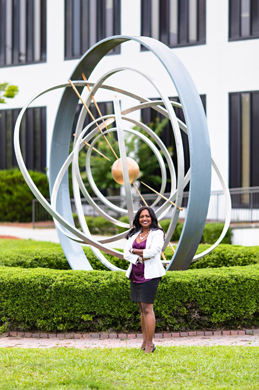 Jhansi Kandasamy in front of the atom at the GE Hitachi Nuclear headquarters in Wilmington, N.C. Photo courtesy WILMA Magazine.